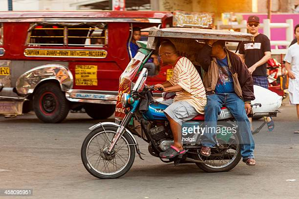 driver and passenger on a motorcycle rickshaw, metro manila - tricycle stock pictures, royalty-free photos & images