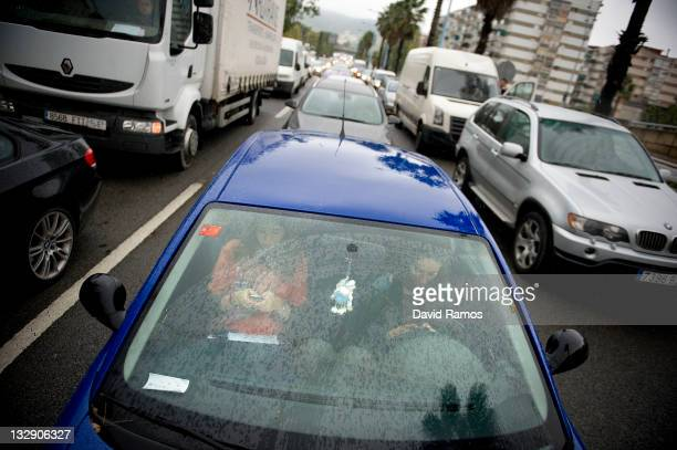 A driver and passenger text messages as they wait in a traffic jam as doctors block one of the Barcelona's main access road during the first day of...