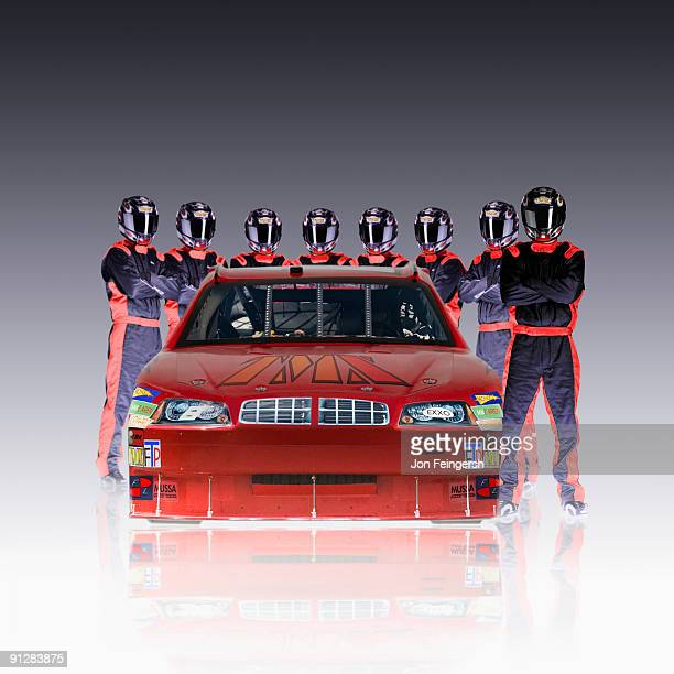 Driver and team standing around nascar.
