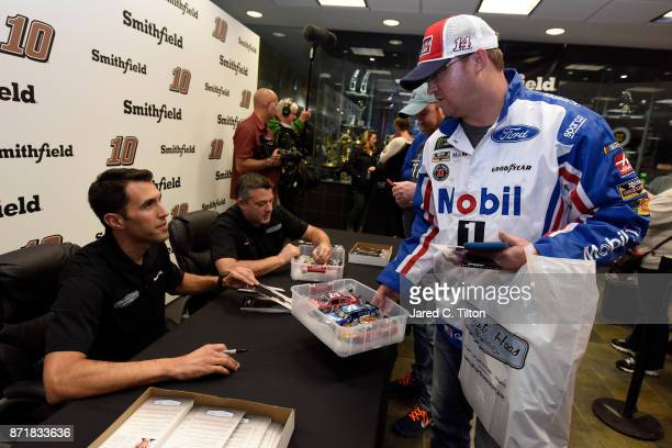 NASCAR driver Aric Almirola and Tony Stewart coowner of StewartHaas Racing sign autographs for fans after a QA session following the StewartHaas...
