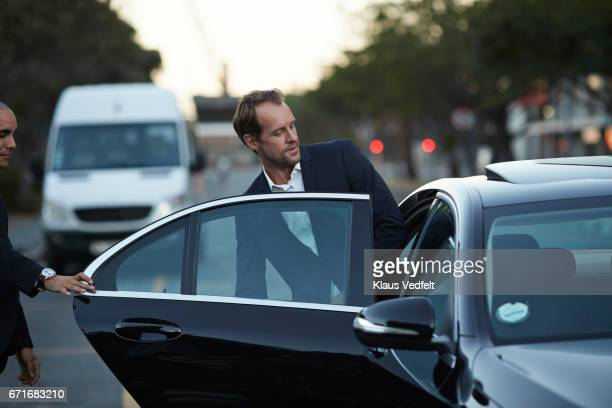 driver assisting businessman into cab - entering stock pictures, royalty-free photos & images