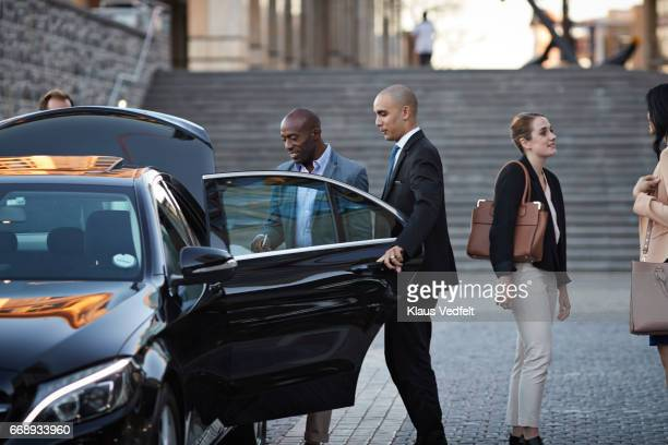 Driver assisting businesspeople into cab