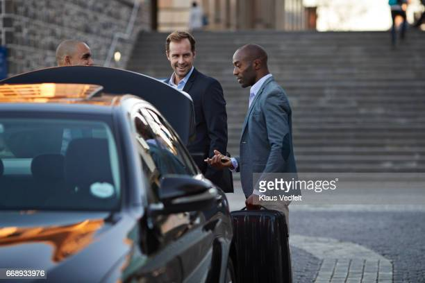 driver assisting businesspeople with luggage at taxi station - white boot stock pictures, royalty-free photos & images