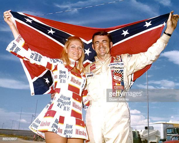 Driver Bobby Allison holds up a confederate flag with Miss Winston Noneen Hulbert before the Alamo 500 race at the Texas World Speedway in College...