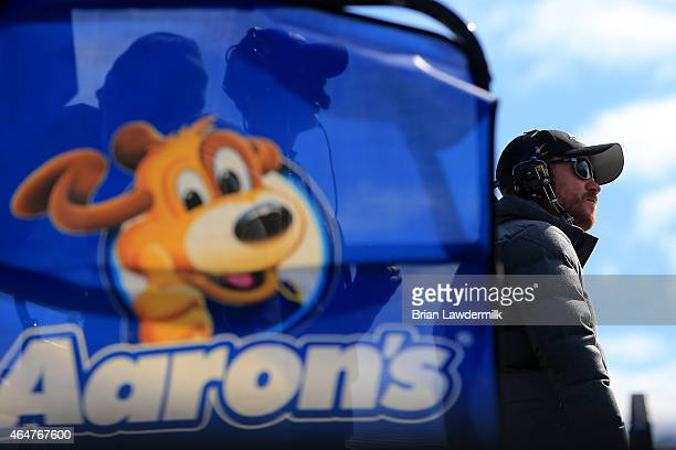 Driver Brian Vickers stands on top of the Aaron's 60th Anniversary Dream Machine Toyota hauler during practice for the NASCAR Sprint Cup Series Folds...