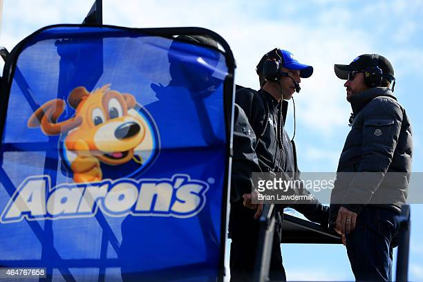 Driver Brian Vickers talks to crew chief Billy Scott on top of the Aaron's 60th Anniversary Dream Machine Toyota hauler during practice for the...