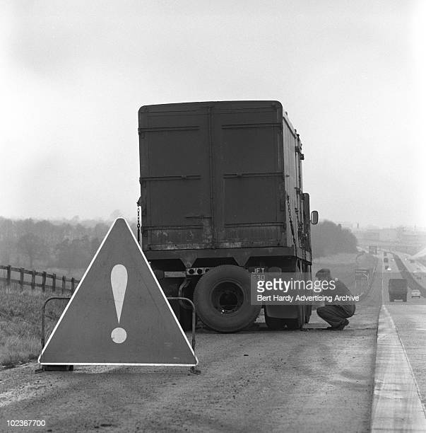 A driver changes a tyre on a motorway near Stevenage in Hertfordshire 6th February 1965