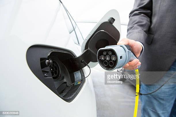 A driver charges a Volkswagen eGolf electric automobile at a charging station outside the Volkswagen AG factory in Wolfsburg Germany on Friday May 20...