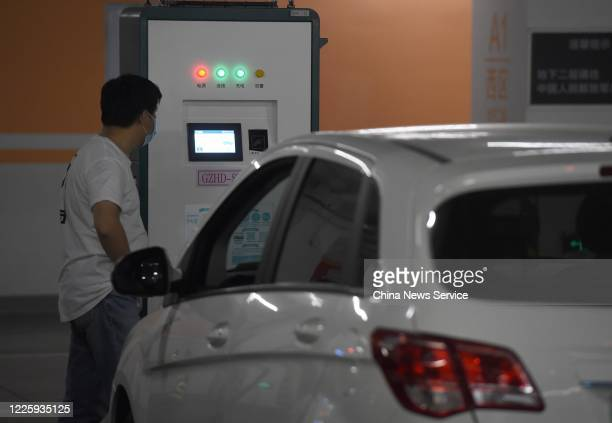 Driver charges his electric car at a charging station set up at the underground parking lot of Cadillac Arena on May 19, 2020 in Beijing, China.