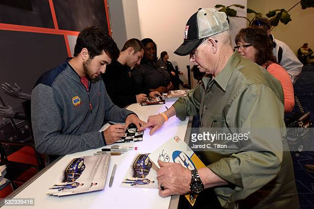 NASCAR driver Chase Elliott signs autographs for fans during the NASCAR Hall of Fame Class of 2017 Fan Appreciation Day at NASCAR Hall of Fame on...
