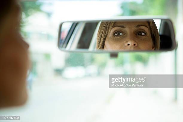 Driver checking rear view mirror
