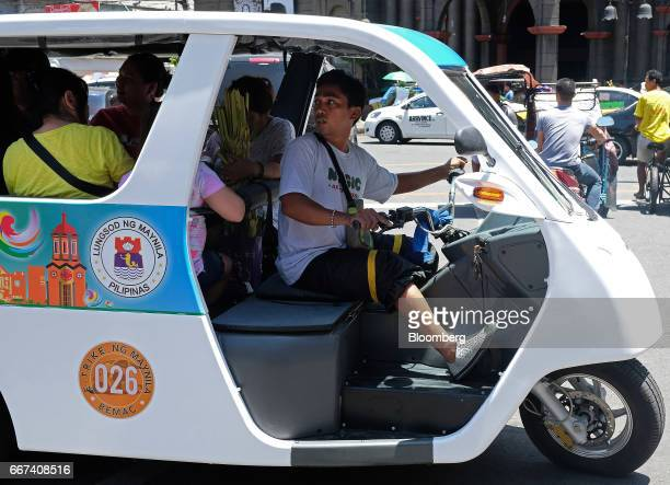 A driver checks on passengers in a Bemac Electric Transportation Philippines Inc ETrike electric tricycle while departing a charging station in...