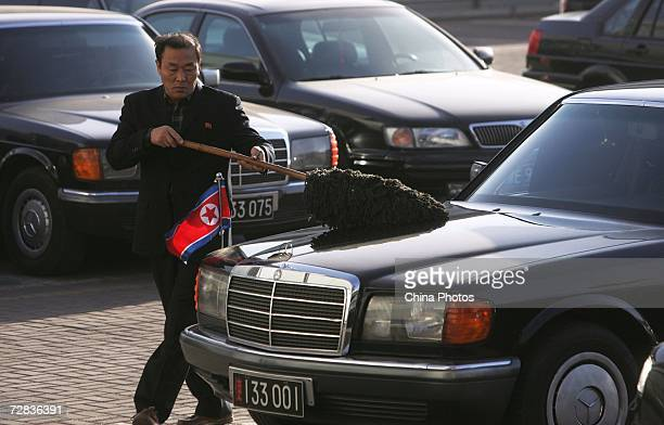 A driver cleans a sedan prepared for North Korean Vice Foreign Minister Kim KyeGwan at the airport December 16 2006 in Beijing China Kim arrived for...