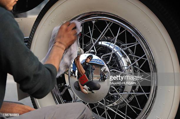 A driver cleans a Stutz car during a vintage car parade in New Delhi on February 13 2012 More than sixty vintage automobiles were on display and...