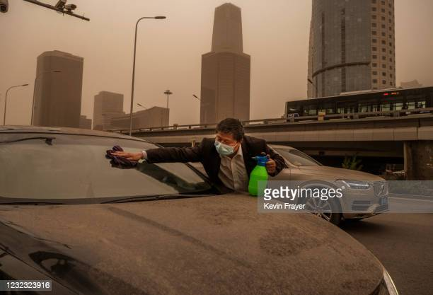 Driver cleans the dirt from sand and rain off of his car during a seasonal sandstorm on April 15, 2021 in Beijing, China. China's capital and the...