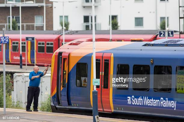 A driver cleans the window of a South Western Railway passenger train operated by Firstgroup Plc in Guildford UK on Monday June 11 2018 FirstGroup...