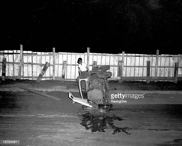 A driver climbs out the window of his Modified stock car following a rollover crash at Greensboro Fairgrounds