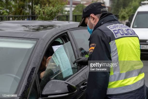 Driver, coming from France, shows his ID and the document authorizing her to cross the border to a Spanish police officer, with a protective face...