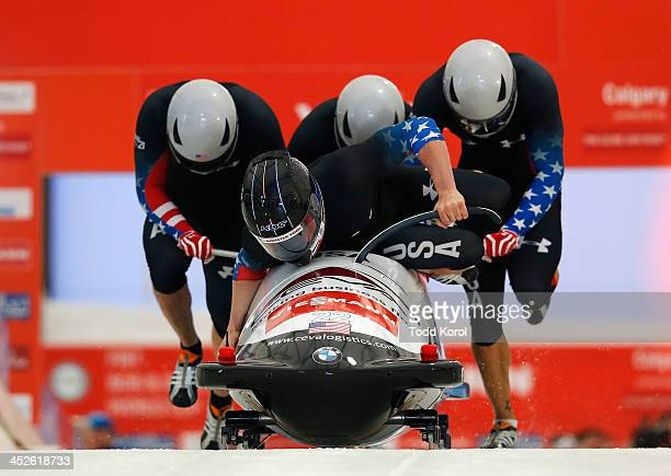 Driver Cory Butner slips and falls on his sled while his teammates Charles Berkeley, Andreas Drbal and Chris Langton of the U.S. Push the sled in the...
