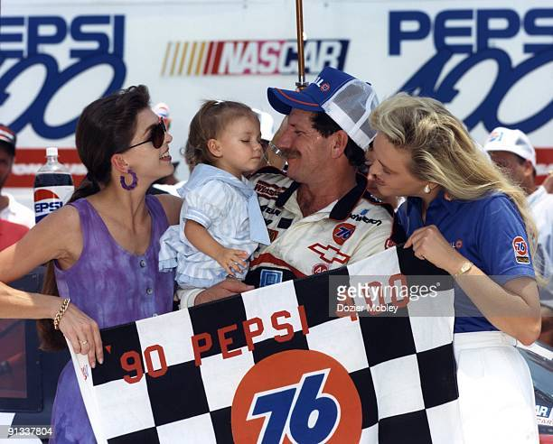Driver Dale Earnhardt and wife Tersea Earnhardt hold their daughter Taylor while celebrating in Victory Lane after winning the Pepsi 400 race on July...