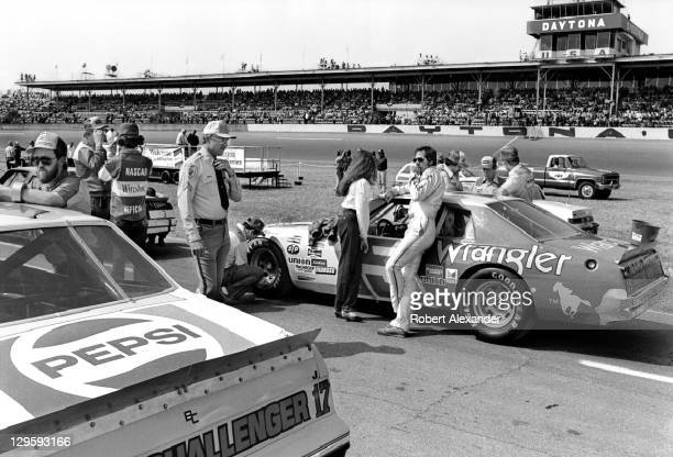 NASCAR driver Dale Earnhardt Sr and his wife Teresa Earnhardt stand beside the Wrangler Cheverolet as a crew member checks the tire pressure prior to...