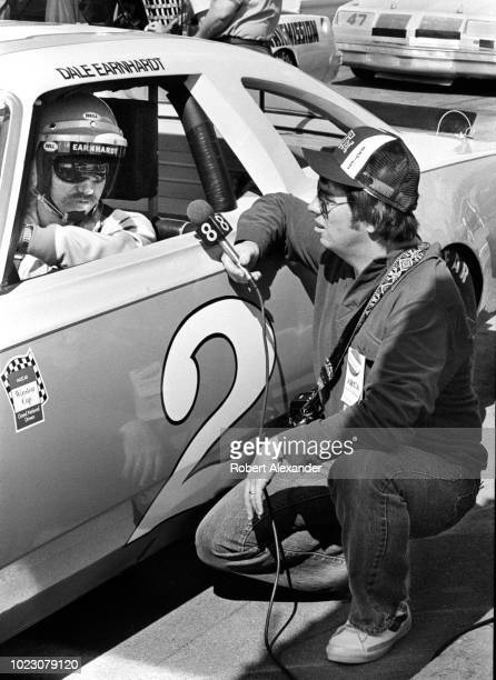 NASCAR driver Dale Earnhardt Sr is interviewed by a television reporter as he sits in his racecar prior to the start of the 1980 Daytona 500 stock...