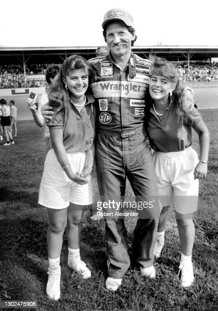 Driver Dale Earnhardt Sr. Poses for a photograph with two young fans prior to the start of the 1981 Firecracker 400 stock car race at Daytona...