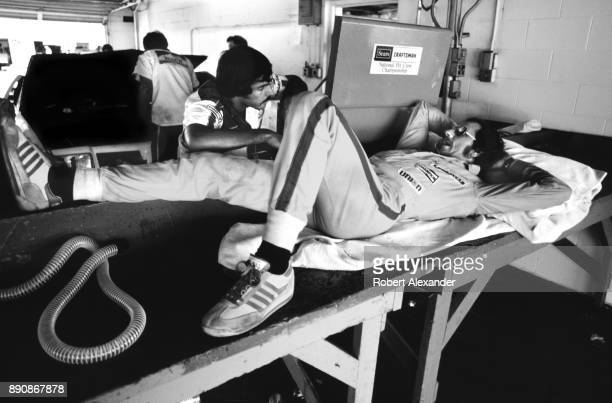 NASCAR driver Dale Earnhardt Sr relaxes and talks with a member of his racing crew Jeff Hammond in the garage prior to the start of the 1980...