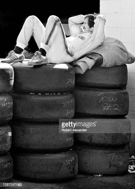 NASCAR driver Dale Earnhardt Sr relaxes on stacks of racing tires in the speedway garage area prior to the start of the 1982 Daytona 500 stock car...
