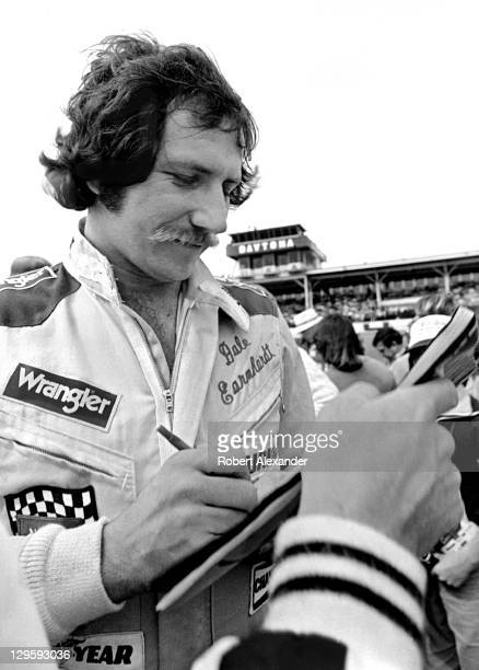 NASCAR driver Dale Earnhardt Sr signs autographs in the infield at the Daytona International Speedway prior to drivers' introductions and the start...