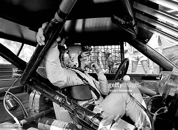 Driver Dale Earnhardt Sr. Sits in his race car while it is repaired after an accident during the 1981 Firecracker 400 on July 4, 1981 at the Daytona...