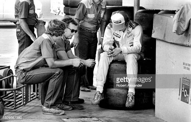 Driver Dale Earnhardt Sr. Sits in the speedway garage with members of his racing team prior to the running of the 1981 Firecracker 400 race at...