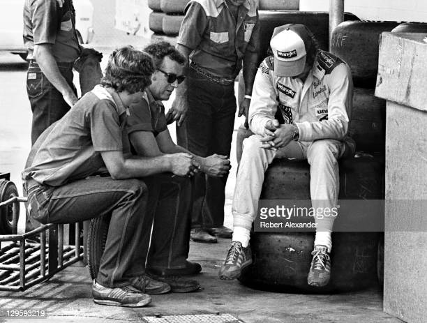 NASCAR driver Dale Earnhardt Sr talks with his crew chief Dale Inman and other racing crew members prior to the start of the 1981 Firecracker 400 at...