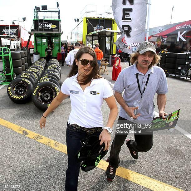 Driver Danica Patrick runs past an autographseeking fan in the garage area before the start of the Nationwide 300 race at Daytona International...