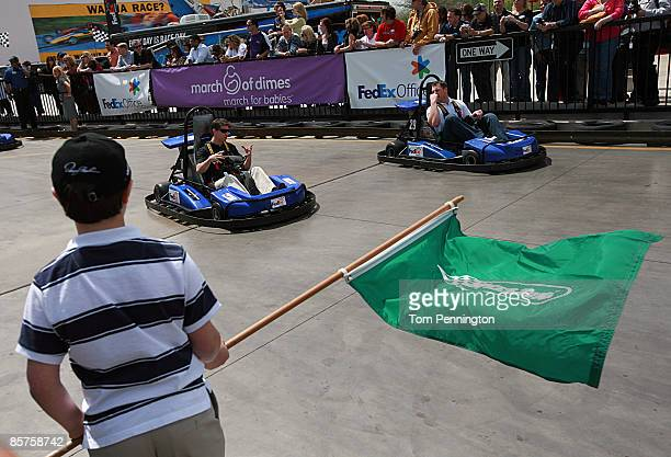 NASCAR driver Denny Hamlin and Dallas Cowboys tight end Jason Whitten prepare to take the green start flag while racing around the track at SpeedZone...