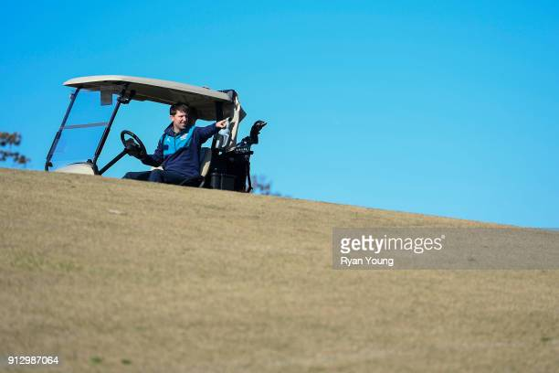 NASCAR driver Denny Hamlin drives a golf cart on the 17th hole at THE PLAYERS Stadium Course at TPC Sawgrass on January 31 2018 in Ponte Vedra Beach...