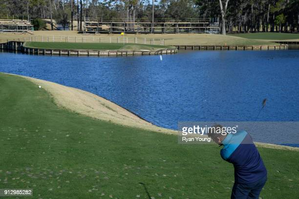 NASCAR driver Denny Hamlin hits balls on the 17th hole at THE PLAYERS Stadium Course at TPC Sawgrass on January 31 2018 in Ponte Vedra Beach Florida
