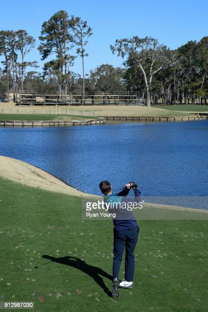 NASCAR driver Denny Hamlin plays on the 17th hole at THE PLAYERS Stadium Course at TPC Sawgrass on January 31 2018 in Ponte Vedra Beach Florida