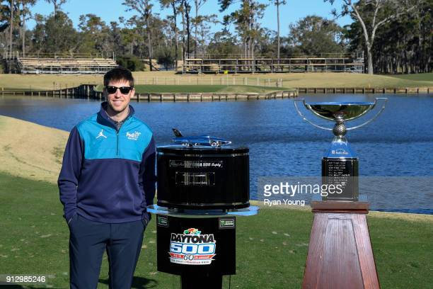 NASCAR driver Denny Hamlin poses with the Daytona 500 and FedEx Cup trophies on the 17th hole at THE PLAYERS Stadium Course at TPC Sawgrass on...