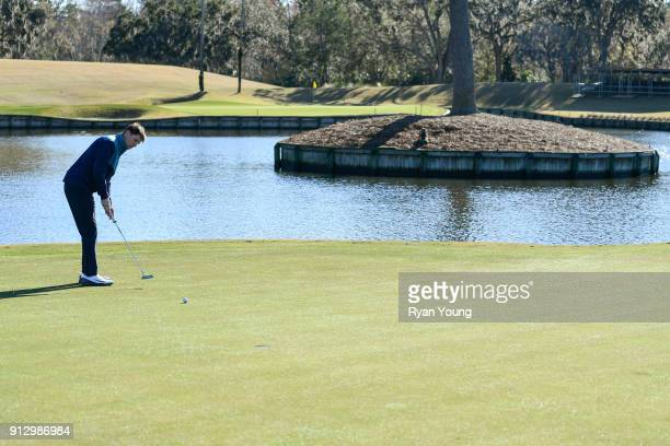 NASCAR driver Denny Hamlin putts on the 17th hole at THE PLAYERS Stadium Course at TPC Sawgrass on January 31 2018 in Ponte Vedra Beach Florida