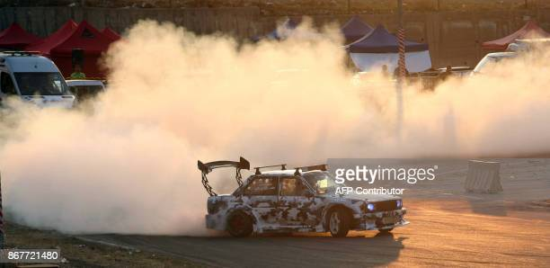 A driver displays his drifting skills during the Middle East Drift Championship at Sofex Circuit in the Jordanian capital Amman on October 27 2017 /...