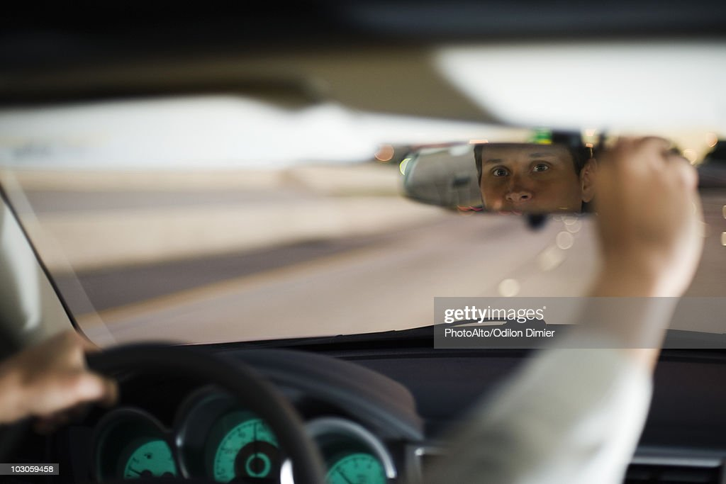 Driver driving adjusting rearview mirror : Stock Photo