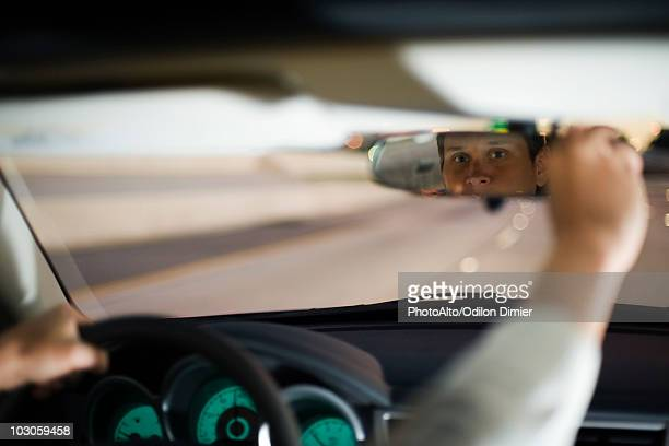 Driver driving adjusting rearview mirror