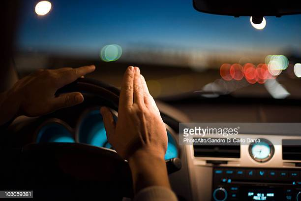 Driver drumming hands on steering wheel