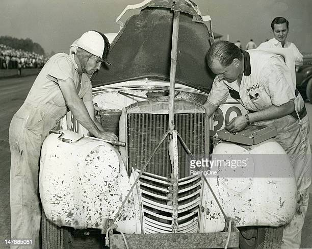 Driver Ed Samples looks on as his mechanic Bob Osiecki makes adjustments to the engine of his Modified stock car before a race at Greensboro...