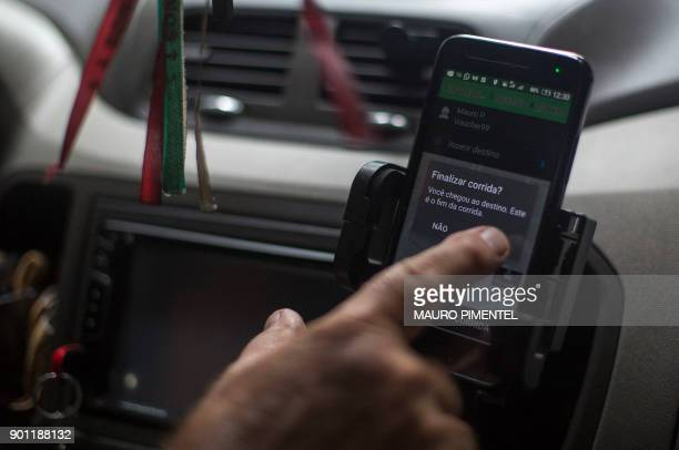 A driver ends a ride taken with the Brazilian App for ridesharing 99 Taxi in Rio de Janeiro Brazil on January 4 2018 Chinese ridehailing giant Didi...