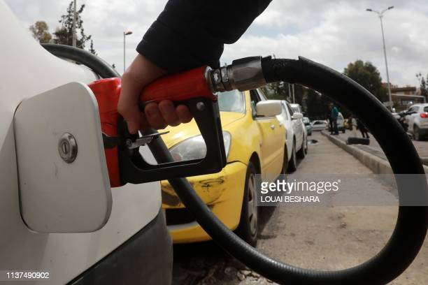 Driver fills his car with gasoline after queueing in front of a petrol station in the Syrian capital Damascus on April 16, 2019. - Syria adopted new...
