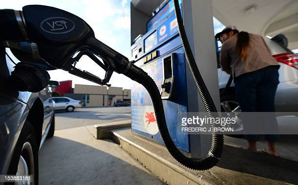 A driver fills ups her tank as cars pull up to a gas station in Alhambra east of downtown Los Angeles on October 10 2012 in California where the...