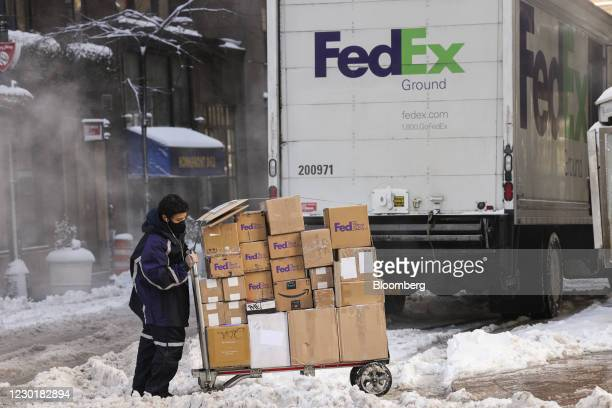 Driver for an independent contractor to FedEx Corp. Pushes a cart of packages through snow in New York, U.S., on Thursday, Dec. 17, 2020. Winter...