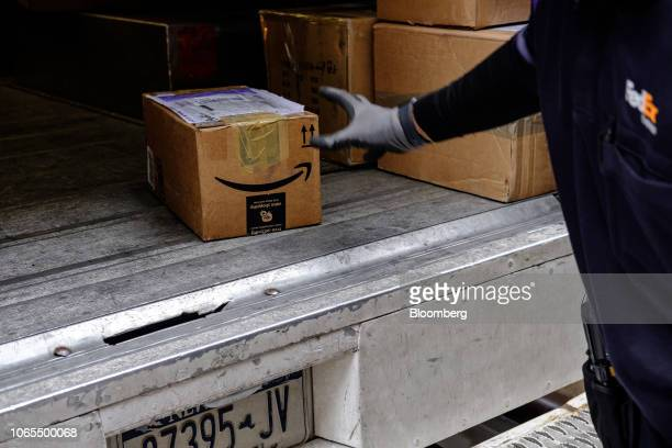 A driver for an independent contractor to FedEx Corp unloads an Amazoncom Inc package from a delivery truck in New York US on Monday Nov 26 2018...
